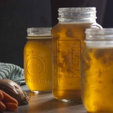 3 glass jars of homemade chicken stock