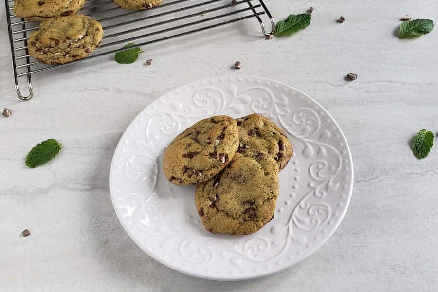 three mint chocolate chip cookies on a white plate
