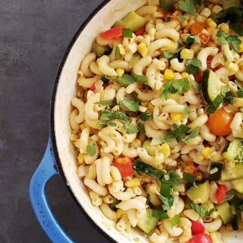 tomatoes and macaroni with summer vegetables in a blue dutch oven