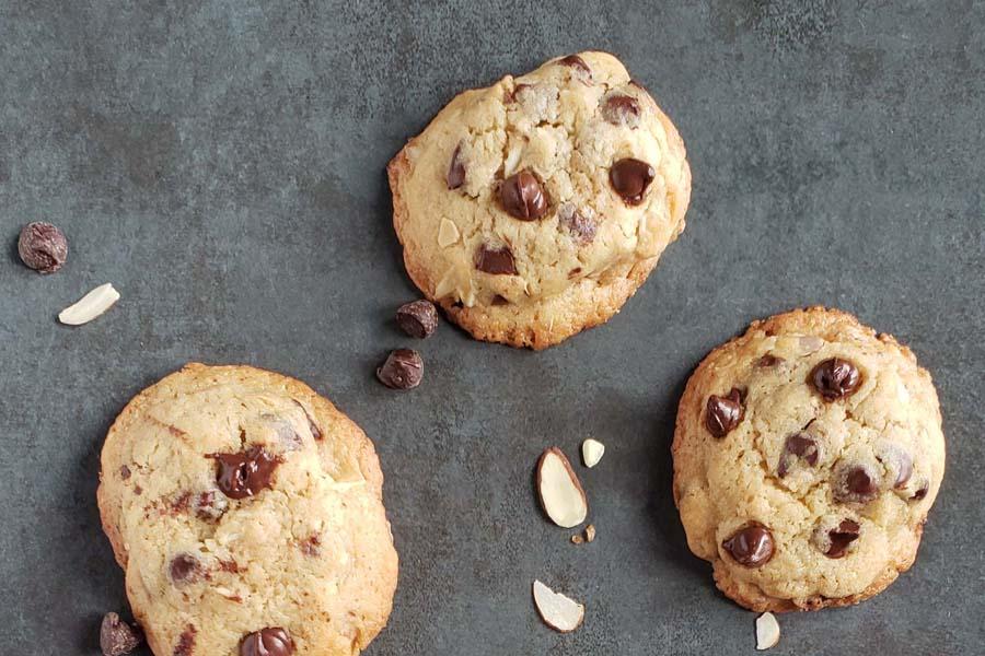 three amaretto chocolate chip cookies on a dark background