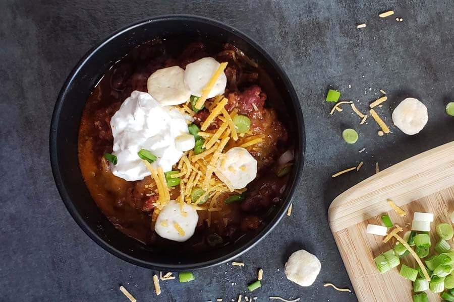 chili in a black bowl topped with cheese, sour cream, and green onions