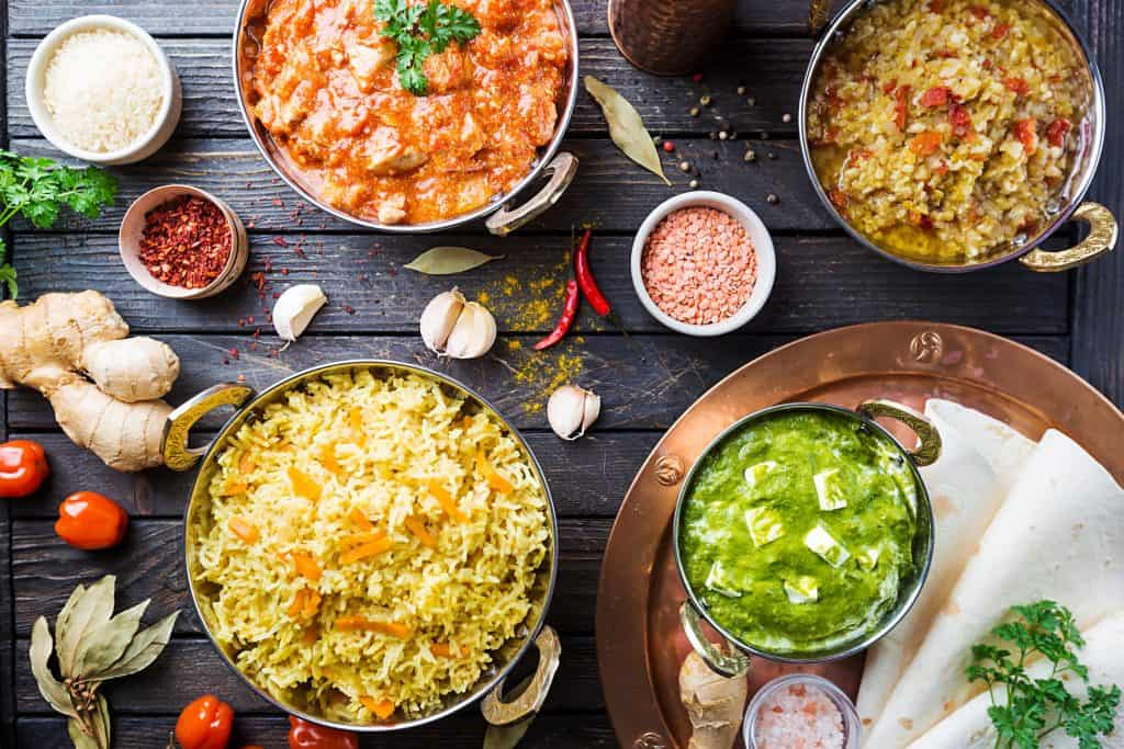 Different bowls with assorted indian food on dark wooden background, top view.