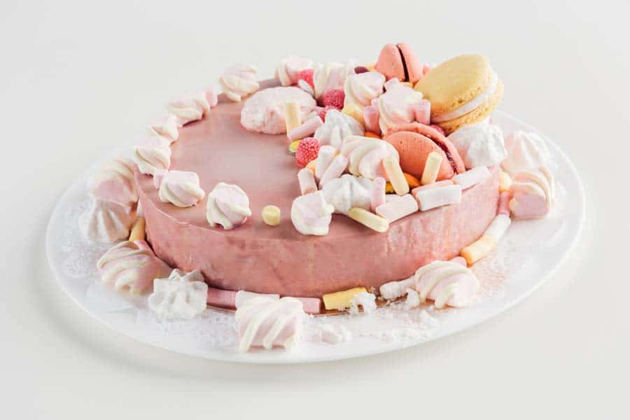 Close up of pink cake with marshmallows and macarons on white plate