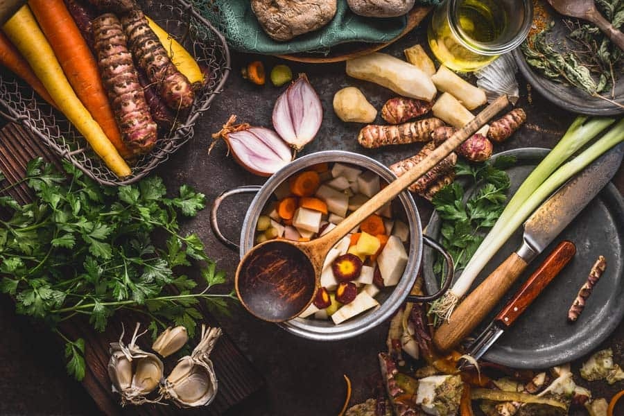 Pot with sliced colorful vegetables and cooking spoon on dark rustic table background with organic vegetarian ingredients and kitchen tools , top view.