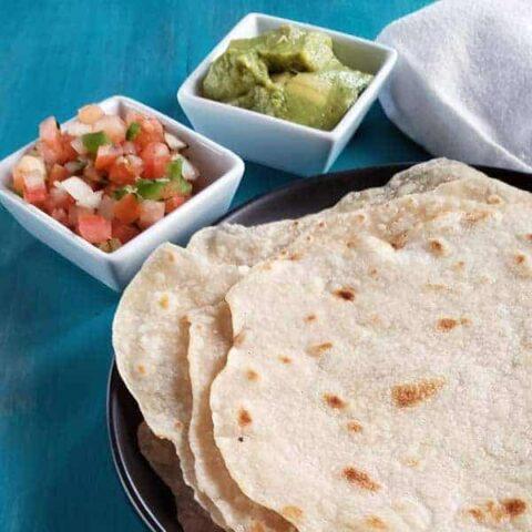 close up of sourdough flour tortillas on a blue background