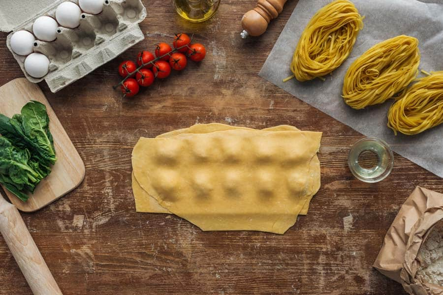 Top view of dough with filling and ingredients for ravioli at wooden table
