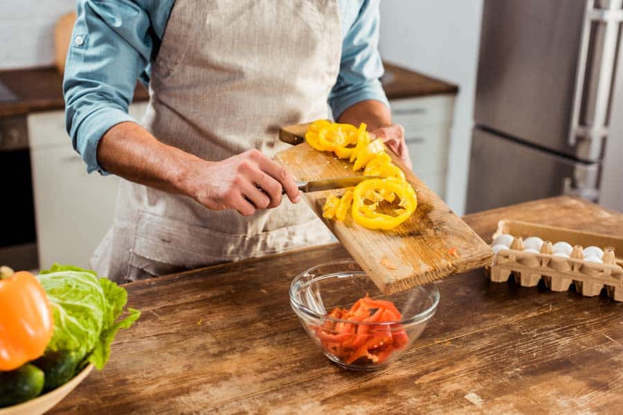 Mid section of man in apron cooking vegetable salad in kitchen