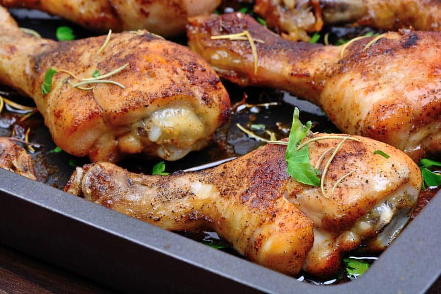 Many chicken legs in pan on wooden table