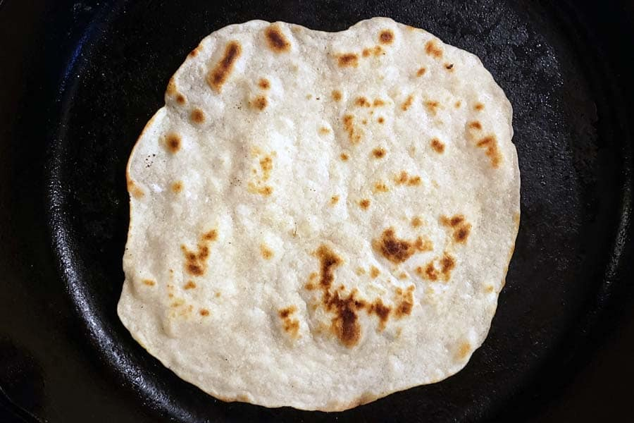 cooking second side of tortilla in a cast iron skillet