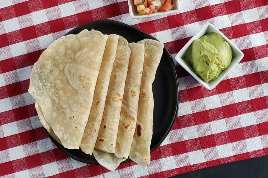 cooked sourdough flour tortillas on a black plate