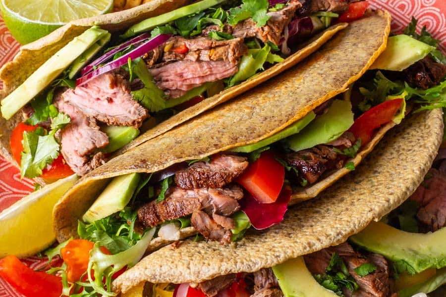 Fresh tacos with beef, avocado slices and peppers served with lime slice on white wooden background