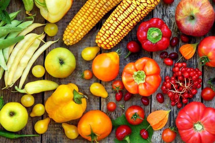 green, red, yellow, purple vegetables and fruits on a wood background