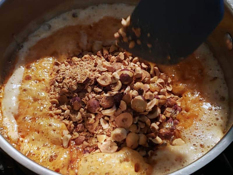 adding hazelnuts to boiling sugar