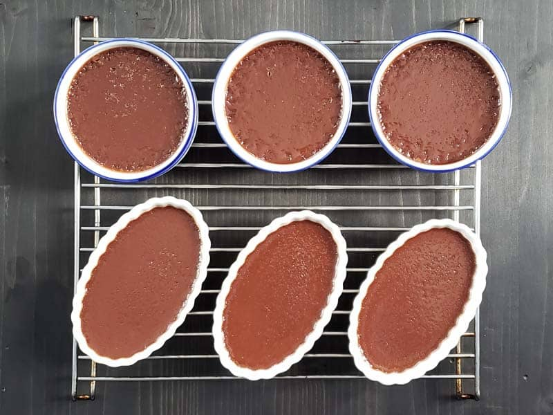 cooked creme brulees cooling on a wire rack