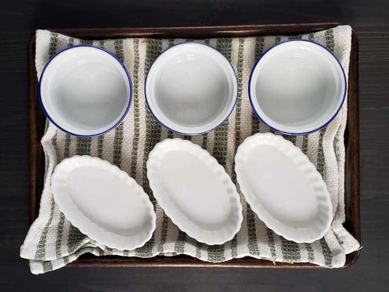 empty ceramic ramekins in a towel lined baking pan