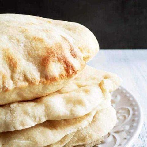 stack of sourdough pita bread on a white plate