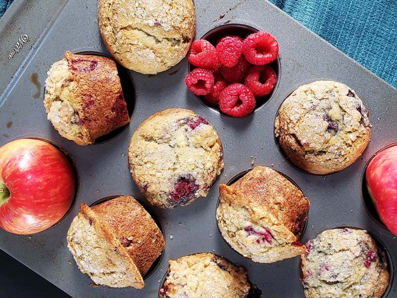 muffins raspberries and apples in a muffin tin