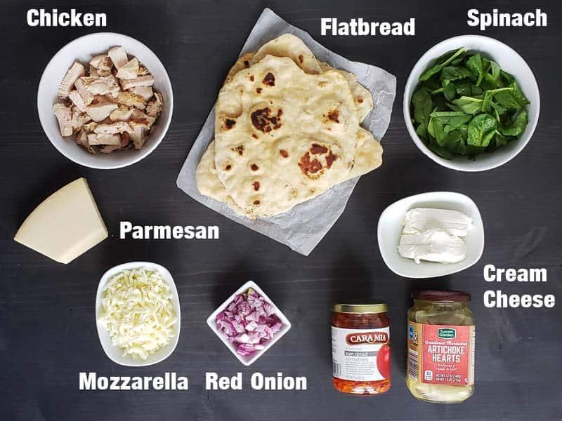 chicken artichoke flatbread ingredients on a dark background