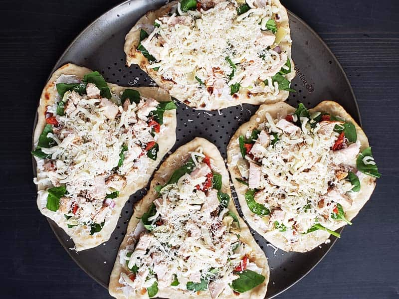 uncooked chicken artichoke flatbreads on a pizza pan