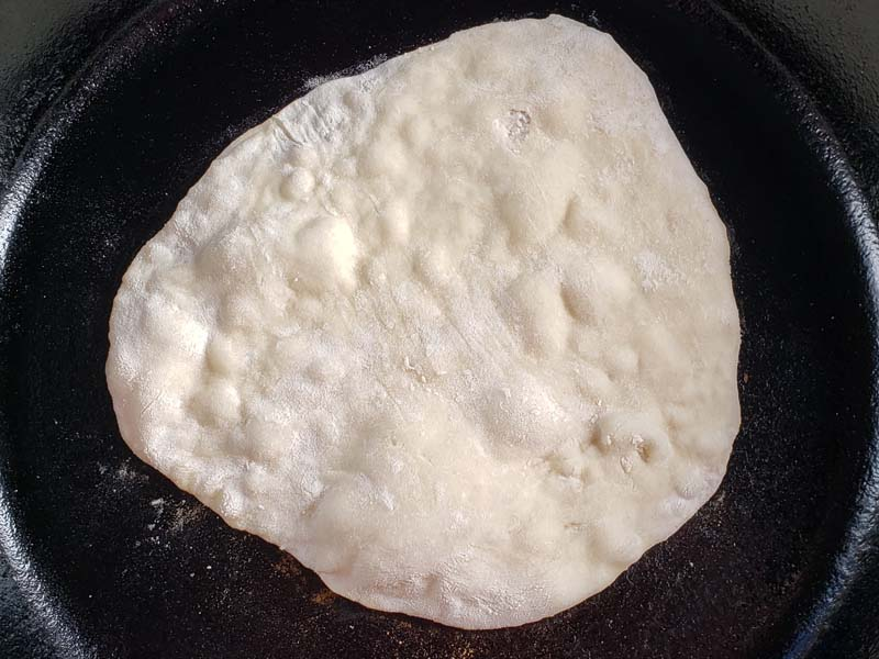 flatbread cooking in cast iron skillet