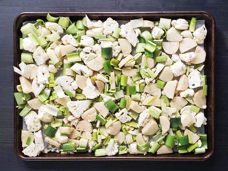 Raw cauliflower, potatoes, leeks, and celery on a baking sheet