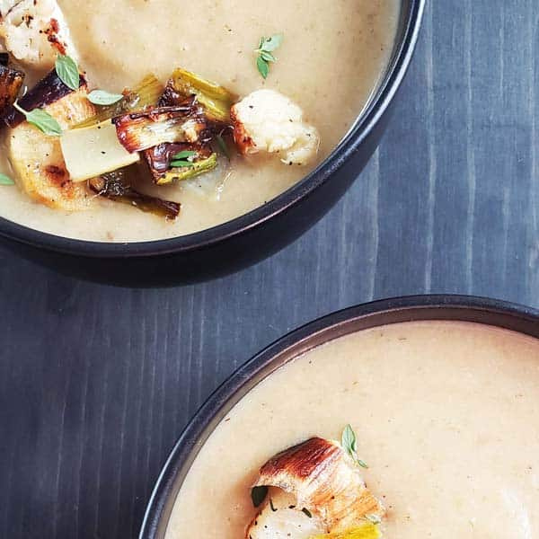 close up of two black bowls filled with roasted cauliflower leek potato soup