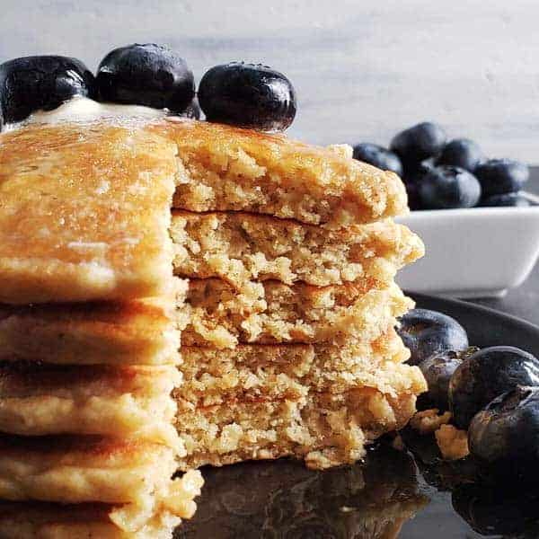 close up of a stack of sourdough oatmeal pancakes topped with blueberries