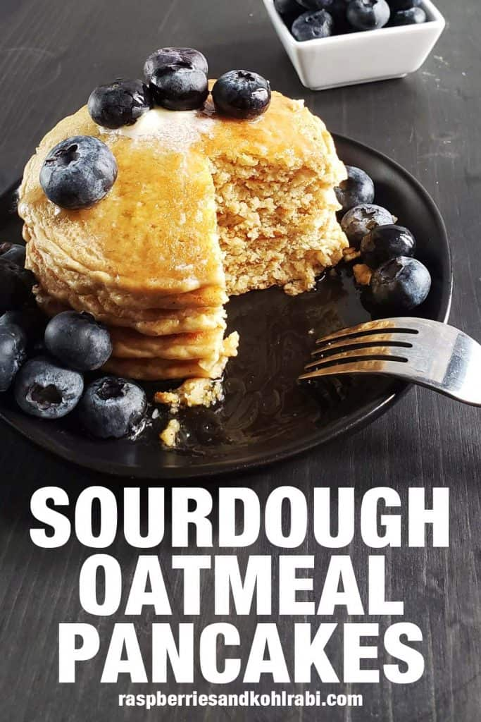 stack of sourdough oatmeal pancakes topped with blueberries on a black plate