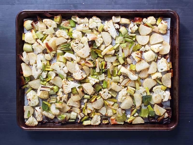 Roasted cauliflower, potatoes, leeks, and celery on a baking sheet