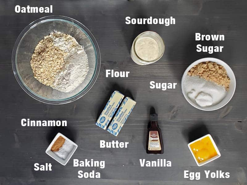 sourdough oatmeal cookie ingredients on a dark background