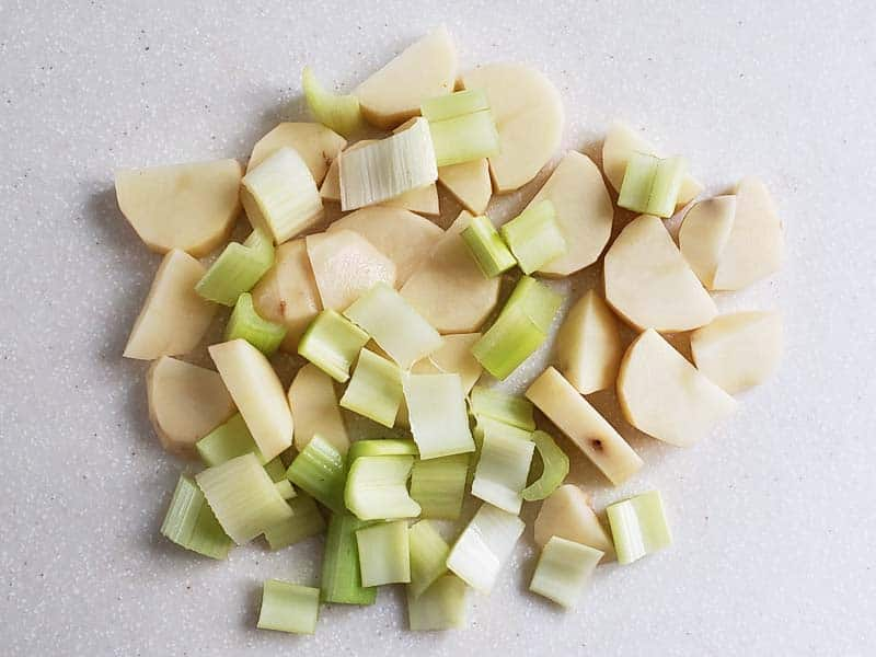 potatoes and celery cut into 1 inch pieces on a white cutting board