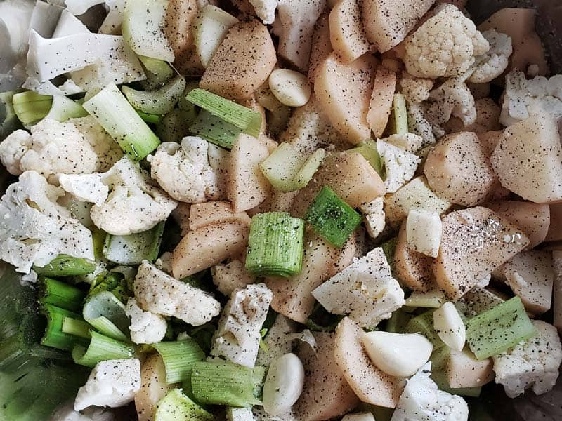 close up of potatoes, cauliflower, leeks, and celery tossed with olive oil