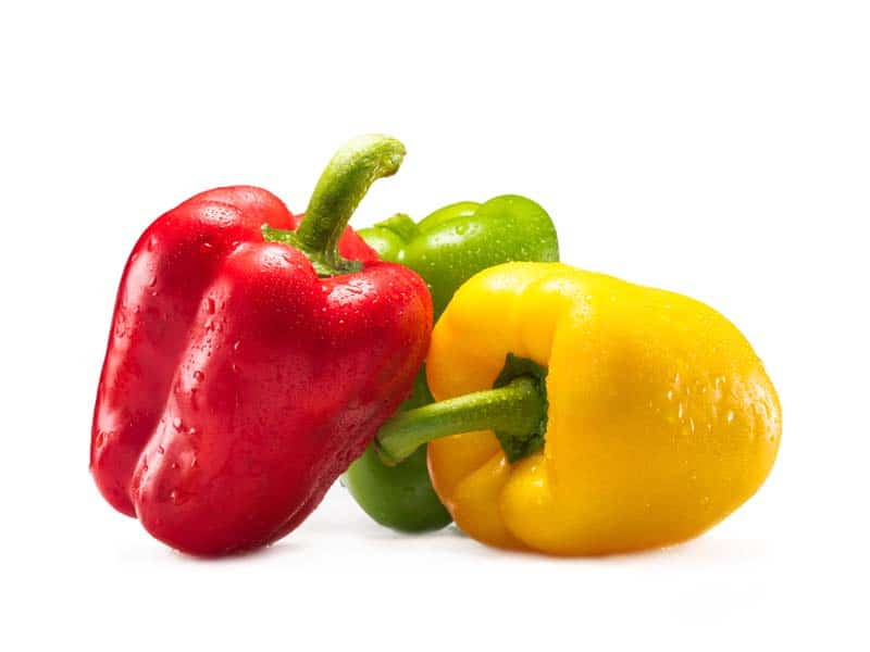 red, green, and yellow bell peppers on a white background