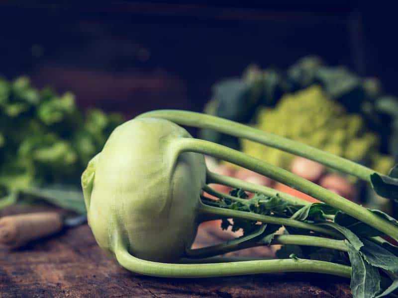 Fresh organic kohlrabi on rustic kitchen table with garden vegetables over wooden background