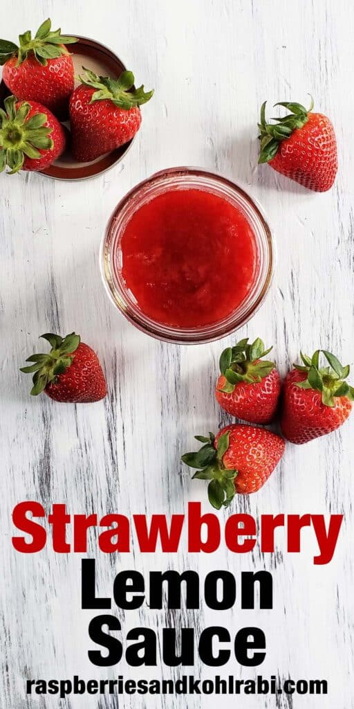top down view of a glass jar of strawberry lemon syrup on a white wood surface surrounded by strawberries