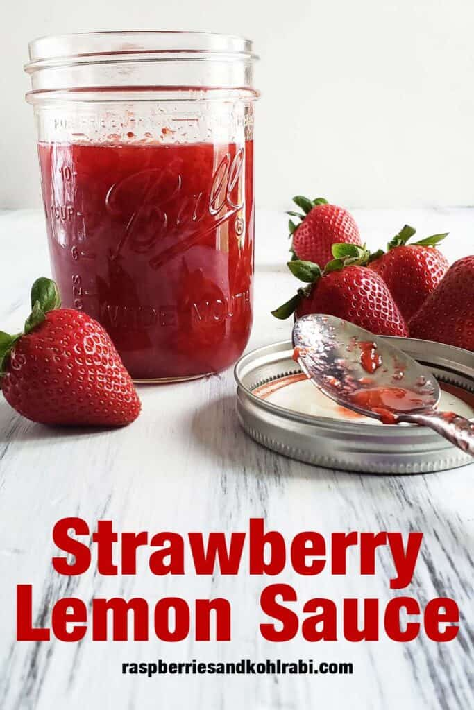 glass jar of strawberry lemon syrup on a white wood surface