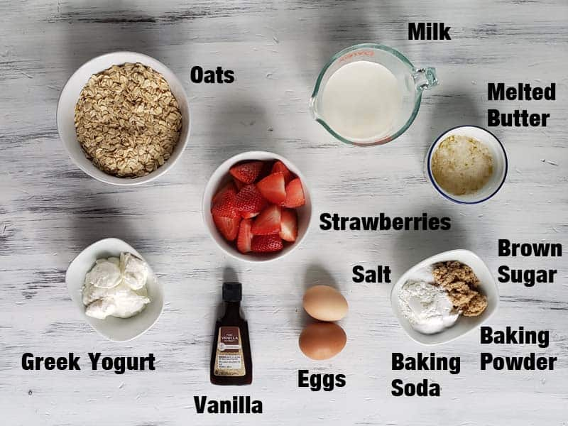 strawberry oatmeal pancake ingredients on a white surface