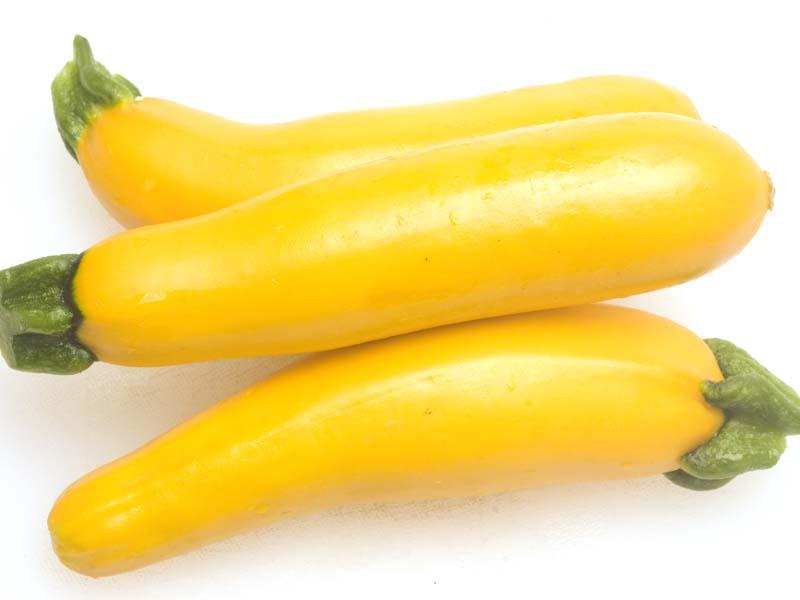 three yellow zucchini squash  on white cutting board