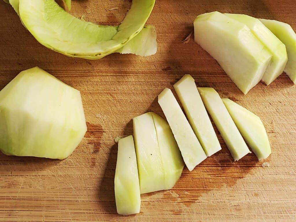 kohlrabi sliced into even 1/2 inch sticks on a wooden cutting board