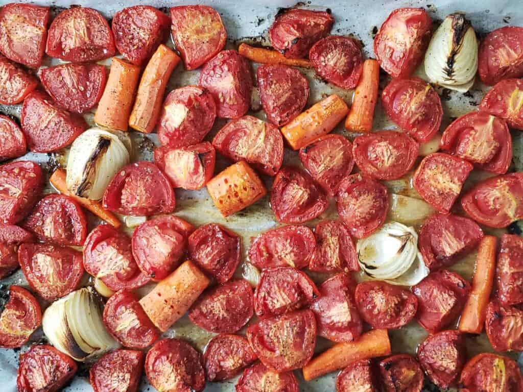roasted tomatoes, onions, and carrots on a sheet pan