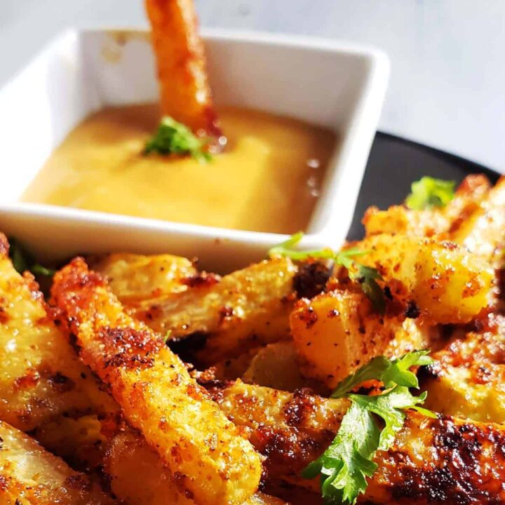 kohlrabi fries on a black plate with dip