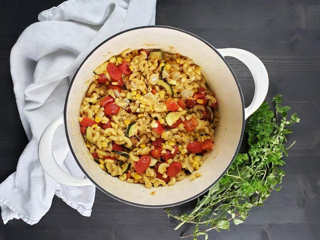 white dutch oven filled with roasted vegetable pasta salad