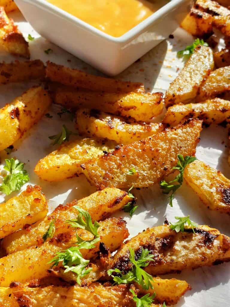 baked kohlrabi fries on parchment paper