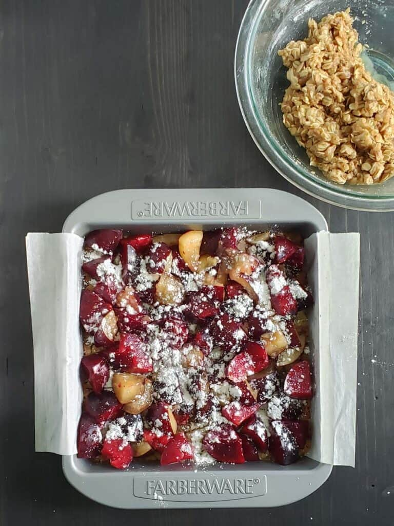 pieces of plum layered in a metal baking dish