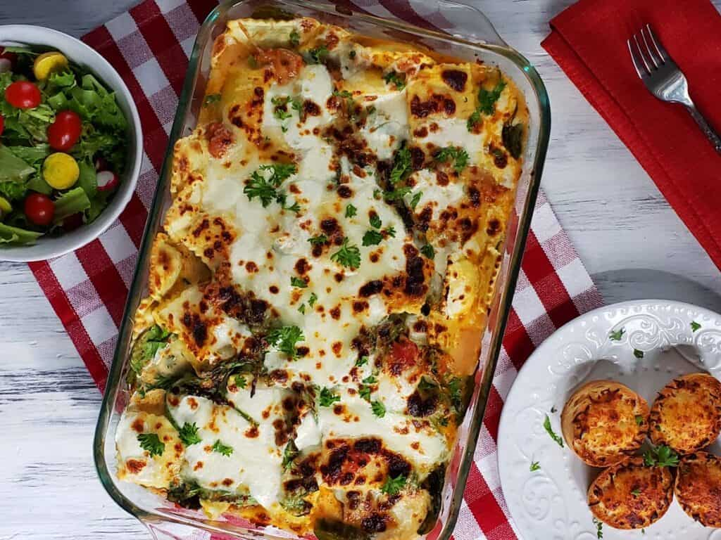 ravioli casserole in a glass baking dish on a white wood background