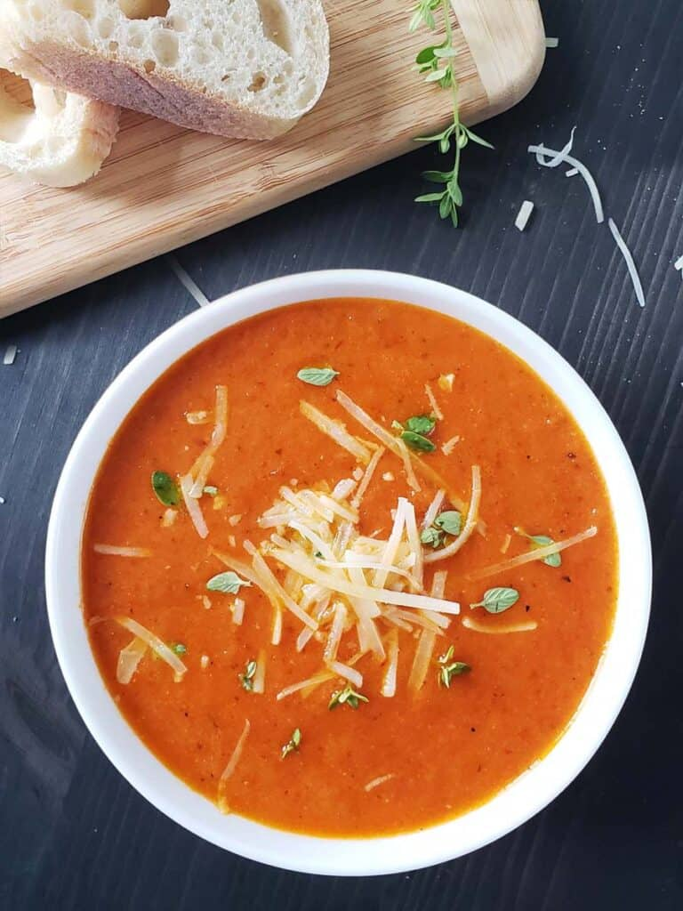 tomato soup in a white bowl on a dark background