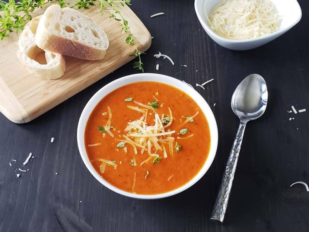 white bowl of tomato soup on a black background