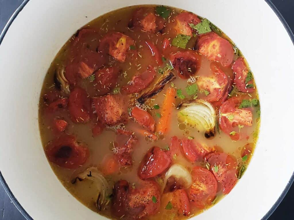 tomato soup ingredients in a white dutch oven