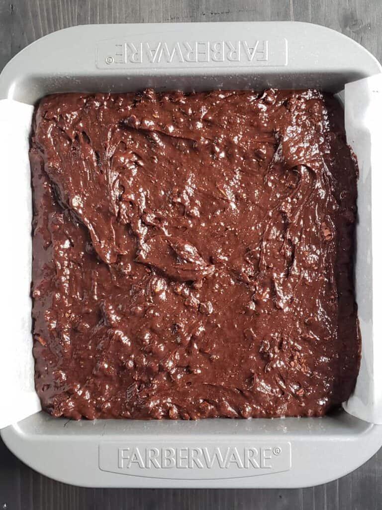 brownie batter in square metal pan