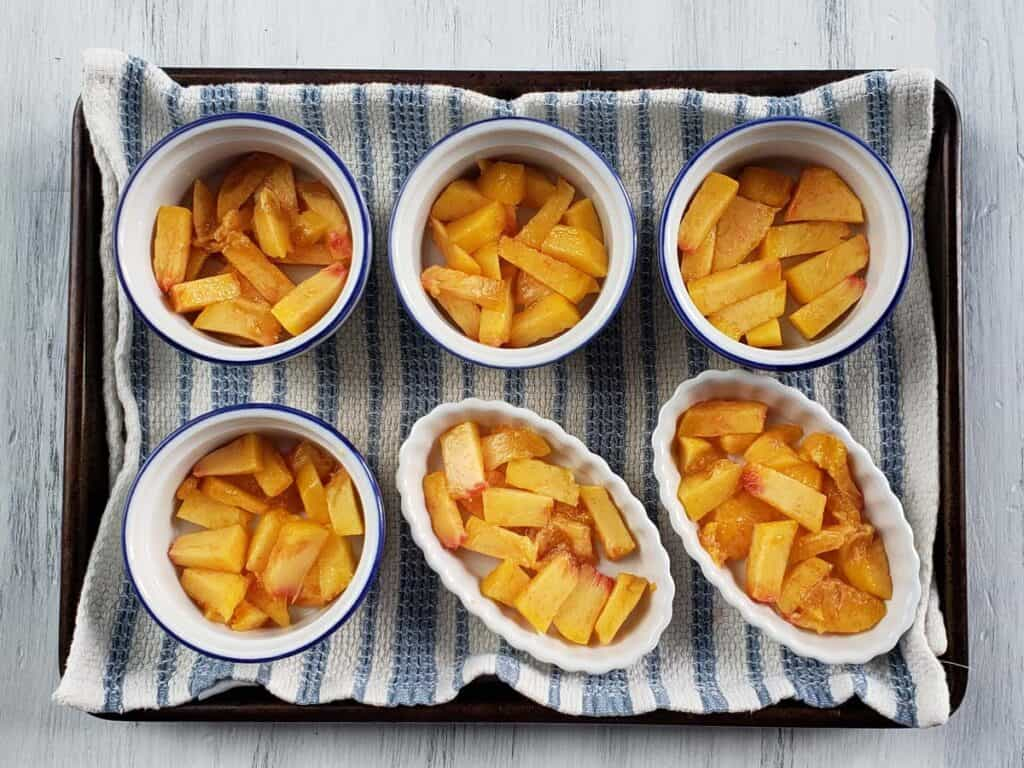 ramekins on a baking sheet filled with chopped peaches